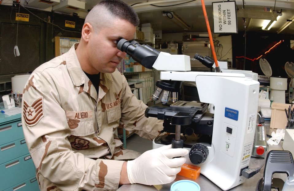 Tech. Sgt. Alex Alverio examines a sample under a high powered microscope at the Air Force Theater Hospital laboratory at Balad Air Base, Iraq. He is deployed here from Wilford Hall Medical Center at Lackland Air Force Base, Texas.